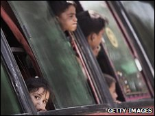 Pakistani children peer out of a bus as they wait to begin the journey to Swat