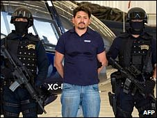 Arnoldo Rueda stands between two armed police officers, on 11 July