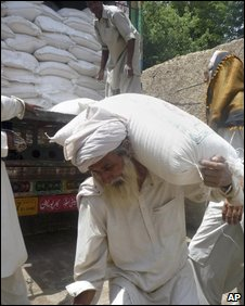 A displaced Pakistani, who fled from the South Waziristan tribal region due to fighting between security forces and Taliban militants, carries a sack of wheat flour after receiving it from a distribution point in Dera Ismail Khan, Pakistan on Tuesday, July 14, 2009. (AP Photo/Ishtiaq Mahsud)