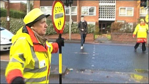 A lollipop lady with sign