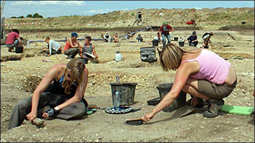 Team members excavate the site