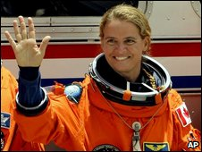 Astronaut Julie Payette, in her orange space suit, waves to the cameras
