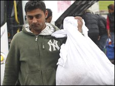 A Roma carries belongings