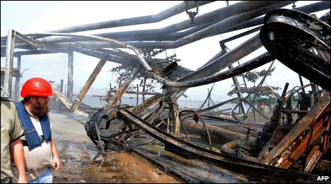 Workers examine wrecked oil pipelines at the Atlas Cove Jetty Depot.