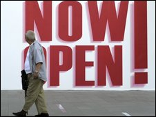A man walks by a billboard promoting a new shopping centre in Beijing - 12 June 2009