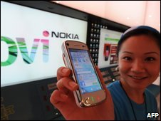 A sales assistant holds up a Nokia handset