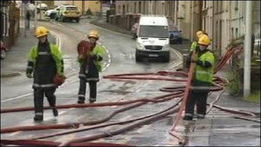 Firefighters pump away flood water