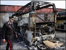 A policeman inspects a burnt bus in southern Italy, April 2008
