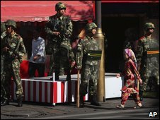 A Uighur girl walks by Chinese security forces in Urumqi, July 16