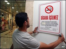 A man hangs a no smoking sign in Istanbul, Turkey (16 July 2009)