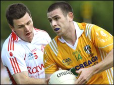 Conor Gormley of Tyrone challenges Antrim forward Sean Burke