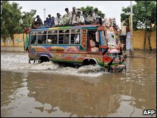 Pakistani commuters travel by bus along a flooded street after heavy monsoon rainfall in Karachi on July 19, 2009