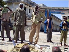 Somali insurgents stand near the bodies of two government soldiers in Mogadishu 13 July 2009