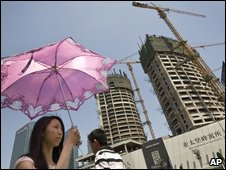 People walking past housing development in Beijing