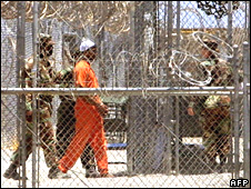 Guantanamo guards with a detainee on 11 January 2002