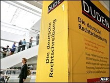 People walk past an oversized Duden dictionary at a Frankfurt book fair in October 2006
