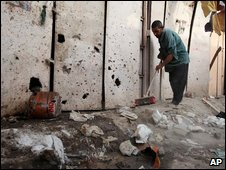 A man sweeps up damage from a bomb in Baghdad (22 July 2009)
