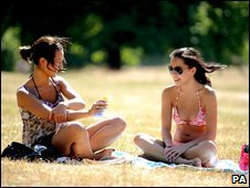 A girl applies sun cream whilst sun bathing with a friend in Hyde Park, London.