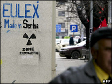 A man walks past anti-EULEX Graffiti in Kosovo