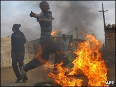 South African residents of Balfour run during riots with police on July 22, 2009