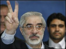 Mir-Hossein Mousavi displays the paint on his fingers after he voted on 12 June