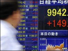 A man walks past a stock market screen in Japan