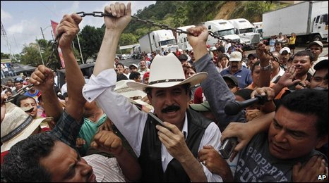 Zelaya, surrounded by supporters and press, lifts the chain at the border in Las Manos, July 24