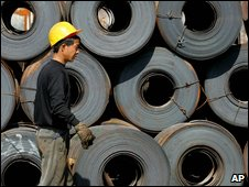 A Chinese worker walks past rolls of steel (file image)