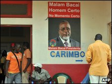 Youths relax near an election poster for Malam Bacai Sanha, candidate for the African Party for the Independence of Guinea and Cape Verde (PAIGC) on June 27, 2009 in Bissau