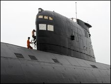 Indian workers (L) paint the conning tower of the INS Kursura, on display as a part of the INS Kurusura Submarine Museum, at Rama Krishna Beach in Visakhapatnam, some 800 kilometers from Hyderabad, on
