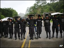 Soldiers blocking a road at Jacagalpa, 85 km west of Tegucigalpa. use their riot shields to keep off the rain, 26 July 2009
