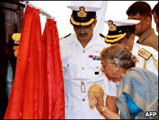 "This handout photograph released by the Ministry of Defence, wife of Indian Prime Minister Manmohan Singh, Gursharan Kaur (foreground R), breaks a coconut on the hull of India""s first nuclear-powered submarine INS Arihant during a ceremony at Visakhapatnam, some 800 kilometers from Hyderabad, on July 26, 2009."