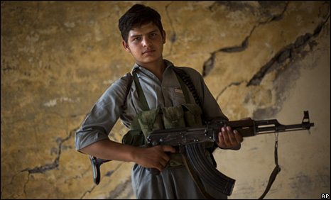 A 13-year-old boy  holds his weapon at the headquarters of a lashkar or local citizens' militia to fight against Taliban militants in Pakistan