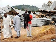 Bystanders look at vandalized buildings in Bauchi, northern Nigeria