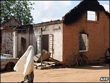 A woman walks past a damaged police station in Potiskum, Yobe State, in 27 July 2009