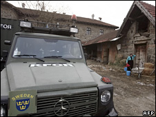 A Serbian woman works near a KFor vehicle in the predominantly-Serb village of Gracanica in Kosovo (16 February 2009)