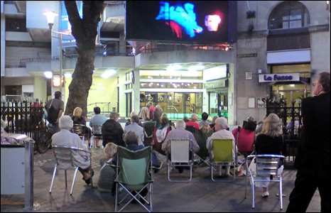 Opera fans watching La Traviata on a big screen outside St Davids Hall in Cardiff (Megan Campbell).