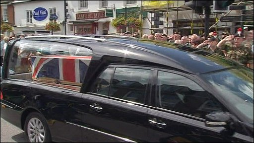 Veterans salute as a cortege carrying the bodies of four dead soldiers processes through Wootton Bassett