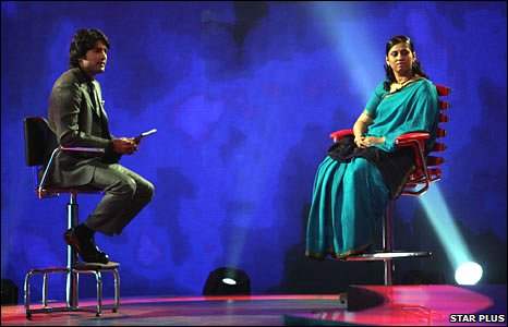 The host of the Sach Ka Saamna TV show sits on a high stool (left), opposite a lady participant