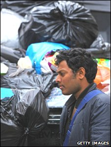 A man walks past pile of rubbish