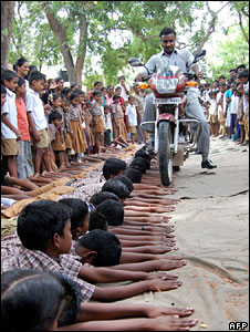 A man driving a motorcycle over the hands of students at a school in Tamil Nadu on 15 July
