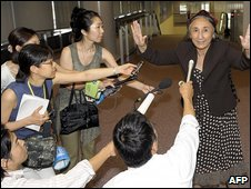 Mrs Kadeer holds up her hands as journalists approach with microphones at Narita airport in Tokyo on Tuesday