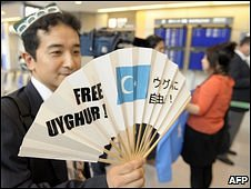 "A supporter of the Uighur cause holds up a large fan with the slogan ""Free Uighur"" at Narita airport in Tokyo, 28 July"