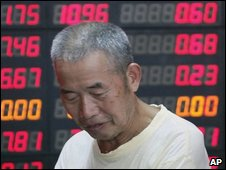 Man standing in front of share information board in Shangha last week