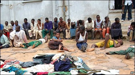 Arrested members of a local Islamic group sit outside a police station