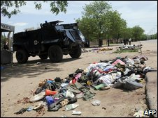 A police car stands near a pile of belongings taken from dead suspected militants in Maiduguri, 29 July