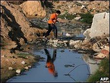 A Palestinian youth walks through a polluted stream near Gaza City (13 June 2009)