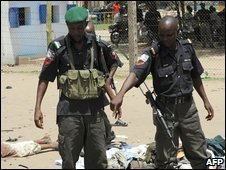 A Nigerian police officer points at a corpse in the northern city of Maiduguri on Wednesday