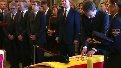 Prime Minister Jose Luis Rodriguez Zapatero places medals on the coffins