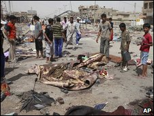 Iraqis gather at the bloodied site of a blast outside a mosque in the Shaab district of north-eastern Baghdad on Friday